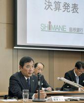記者会見する島根銀行の鈴木良夫頭取(左)=12日午後、松江市