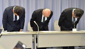 記者会見で頭を下げる静岡県立静岡がんセンターの高橋満病院長(中央)ら=14日午後、静岡県庁