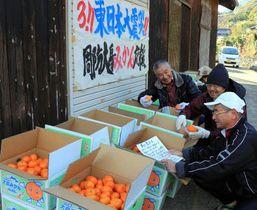 東日本大震災の被災地に送るミカンを荷造りするメンバー