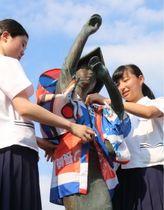 応援のぼりで作った法被を銅像に着用させた諫早農業高生たち=諫早市永昌東町
