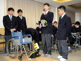 車いすに座ったまま足を動かせるフットレストの説明をする新居浜工業高校の生徒