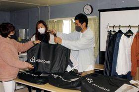 自社衣料のセットを倉敷市真備町地区の女性に手渡すジョンブルの菅野専務(右)