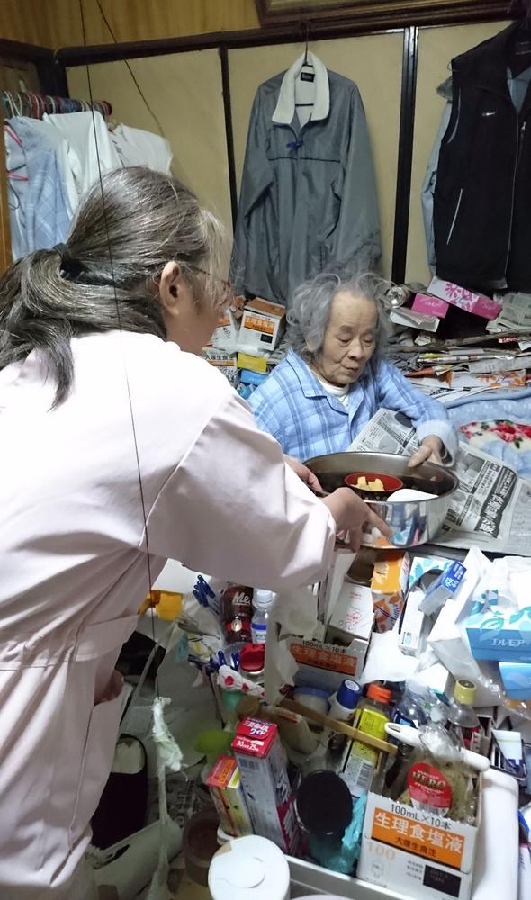 食事の介助をするホームヘルパー(手前)と生活援助サービスを利用する橋本正臣