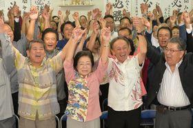 再選を決め、支援者らとバンザイ三唱で喜ぶ城間幹子氏(中央)=21日午後8時すぎ、那覇市松山の選挙事務所