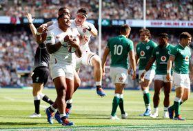 ラグビーのテストマッチ、トライを喜ぶイングランドの選手たち(左)と肩を落とすアイルランドの選手たち=24日、ロンドン(ロイター=共同)