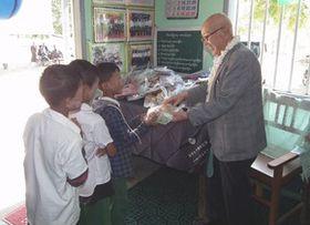 益金で建てられた学校で子どもにプレゼントを渡す山元将生さん(右)