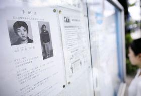 近鉄富田林駅近くの掲示板に張られた樋田淳也容疑者の顔写真入りのチラシ=14日