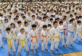 県内101道場から約2100人の子どもたちが出場し、準備運動で元気な声を響かせた=15日、那覇市・県立武道館(古謝克公撮影)
