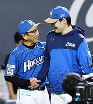 連敗を9で止め、ベンチ前で有原(右)と笑顔で握手する日本ハム・栗山監督=札幌ドーム