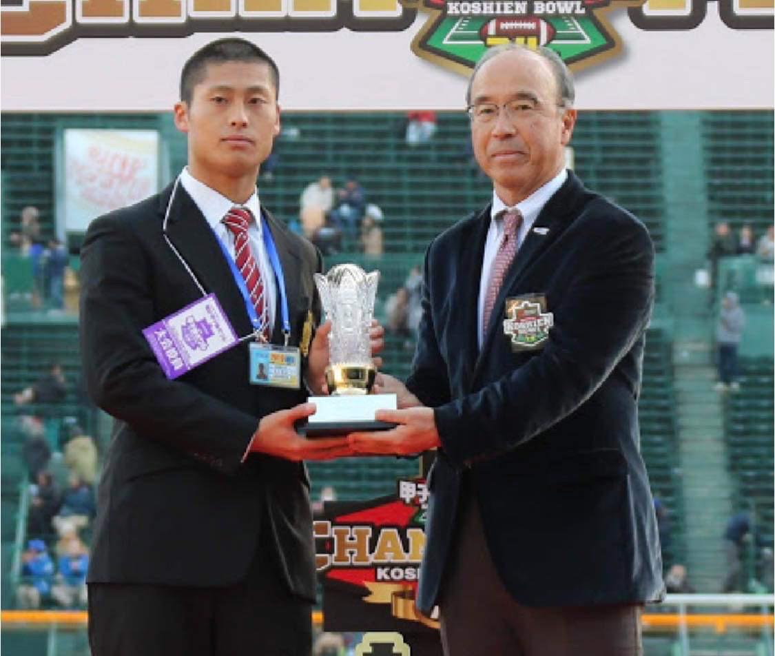 「チャック・ミルズ杯」を手渡される、立命大のQB荒木優也選手。右は国吉誠・日本協会会長=撮影:横地美佳乃