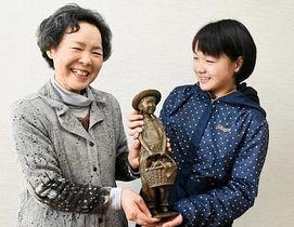 児童とともにブロンズ像を手にする立花さん(左)