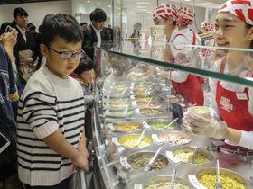 「カップヌードルミュージアム 大阪池田」で具材を選ぶ子ども=18日、大阪府池田市