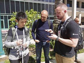 米マイクロソフトの最新アプリを体験し、開発者らと意見交換する野沢幸男さん(左)=14日、米カリフォルニア州アナハイム(共同)