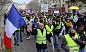 19日、パリの通りを練り歩く黄色いベスト運動のデモ参加者ら(ゲッティ=共同)