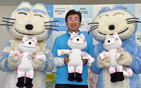 「へんなねこ」の縫いぐるみを手にする松尾町長(中)