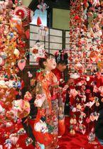 色とりどりの「雛のつるし飾り」を眺める女の子=19日、静岡県東伊豆町(伊豆新聞本社提供)