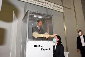 ボックスの中に入り、PCR検査の検体採取のイメージを再現する今院長