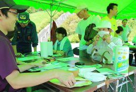 市社協職員(左)らの指導で、キッチンペーパーを使ったマスク作りなどを体験する参加者=対馬市公会堂