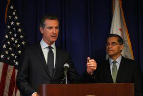 米西部カリフォルニア州サクラメントで記者会見するニューサム知事(左)=18日(ゲッティ=共同)