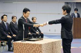 新任検事に辞令を交付する山下法相(左)=17日午前、法務省