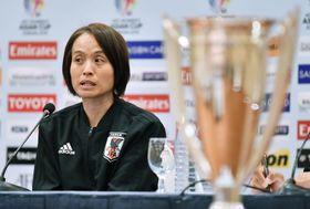 オーストラリアとの決勝戦を前に記者会見するサッカー女子日本代表の高倉監督。右は優勝杯=19日、アンマン(共同)