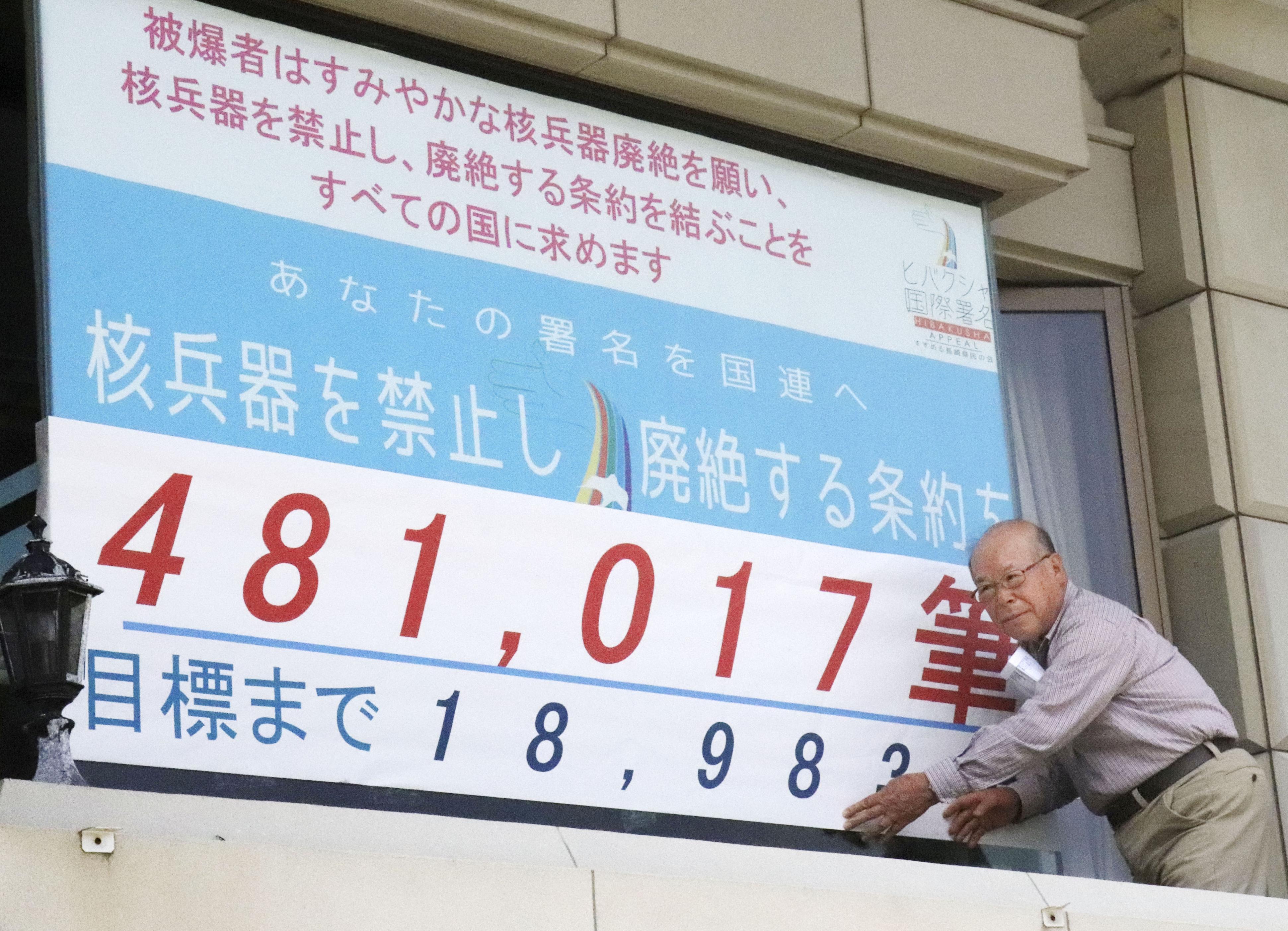 長崎原爆被災者協議会の事務所の窓に、核兵器廃絶を求める「ヒバクシャ国際署名」に集まった署名数を掲示する田中重光さん=27日午後、長崎市