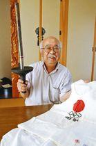 1964年の聖火リレーで使用したトーチとユニホームを手にする中野さん=豊田市常盤町で