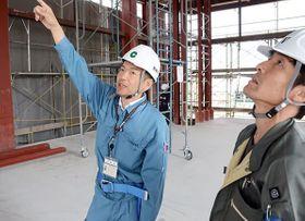 熊本市消防局の増設工事の進み具合を確認する熊本市職員の宮古睦さん(左)。今年4月、正職員に採用された=熊本市中央区