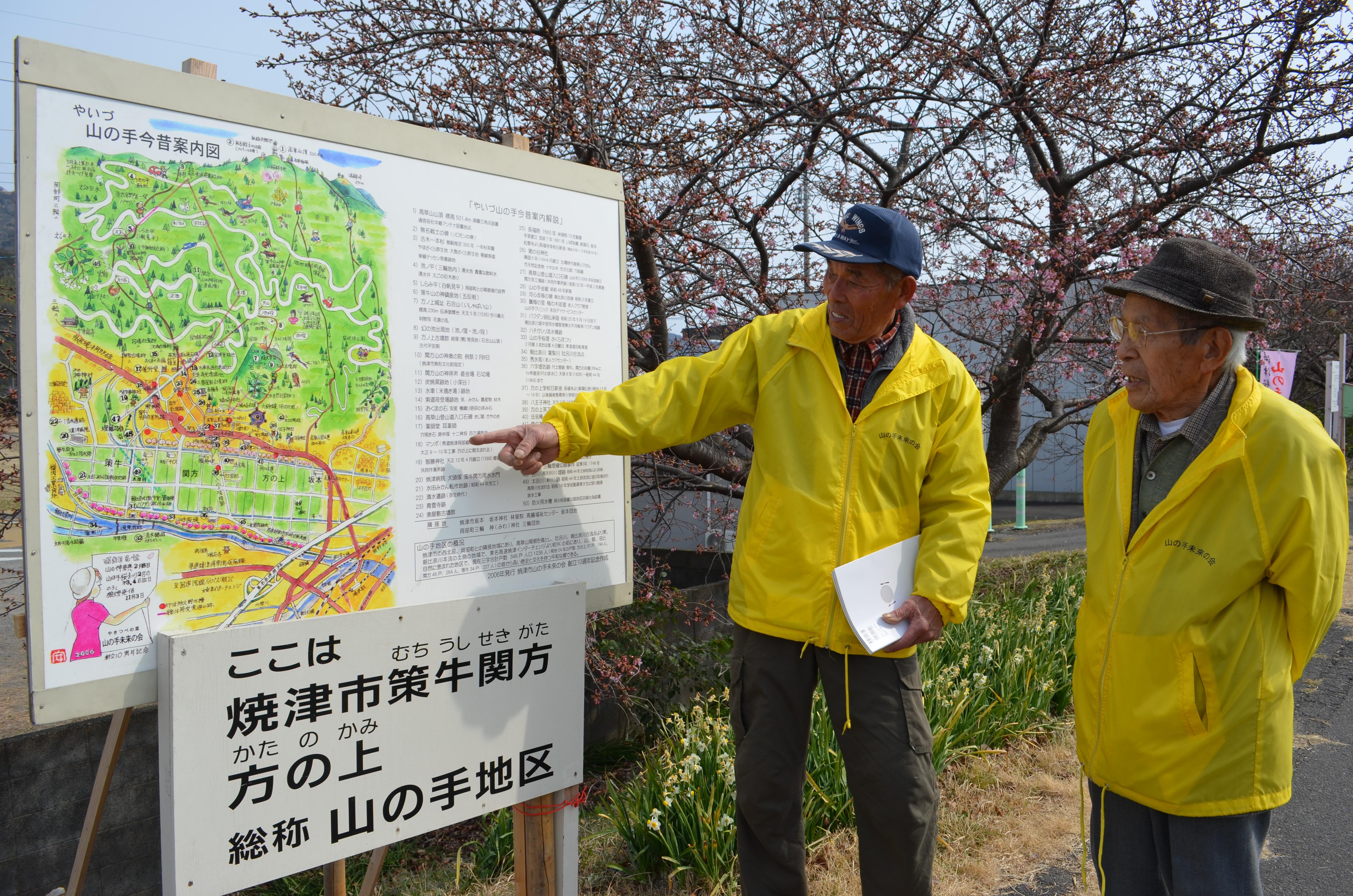 「焼津市山の手未来の会」が設置した案内看板の前で説明する現会長の山田宏さん(左)と初代会長の永田壽男さん(右