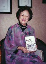 石坂洋次郎生誕100年を記念して弘前で編まれたエッセー集「山のかなたに」を手にして笑顔を見せる杉さん。米ロサンゼルスから関係者に送られてきた=2001年