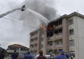 はしご車で消火活動をする消防隊員=14日午後4時半ごろ、吉野川市山川町湯立