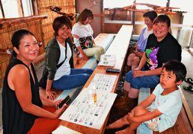 にがり入りの足湯でほっこりする地元の女性や子どもたち=13日、伊江村・にがり足湯