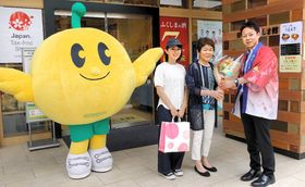 200万人目の来館者となった大橋さん親子に花束を贈る石川館長(右)