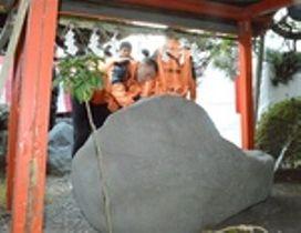 けがのないシーズンを祈り、靴の形をした石に触る清水の選手たち=富士市今井