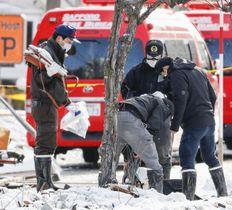 爆発があった現場から消臭スプレー缶を回収する警察官=18日、札幌市豊平区