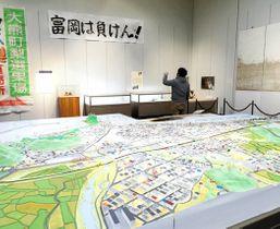 震災前の町を再現したジオラマや津波の痕跡が残る壁紙(右奥)などが展示されている会場