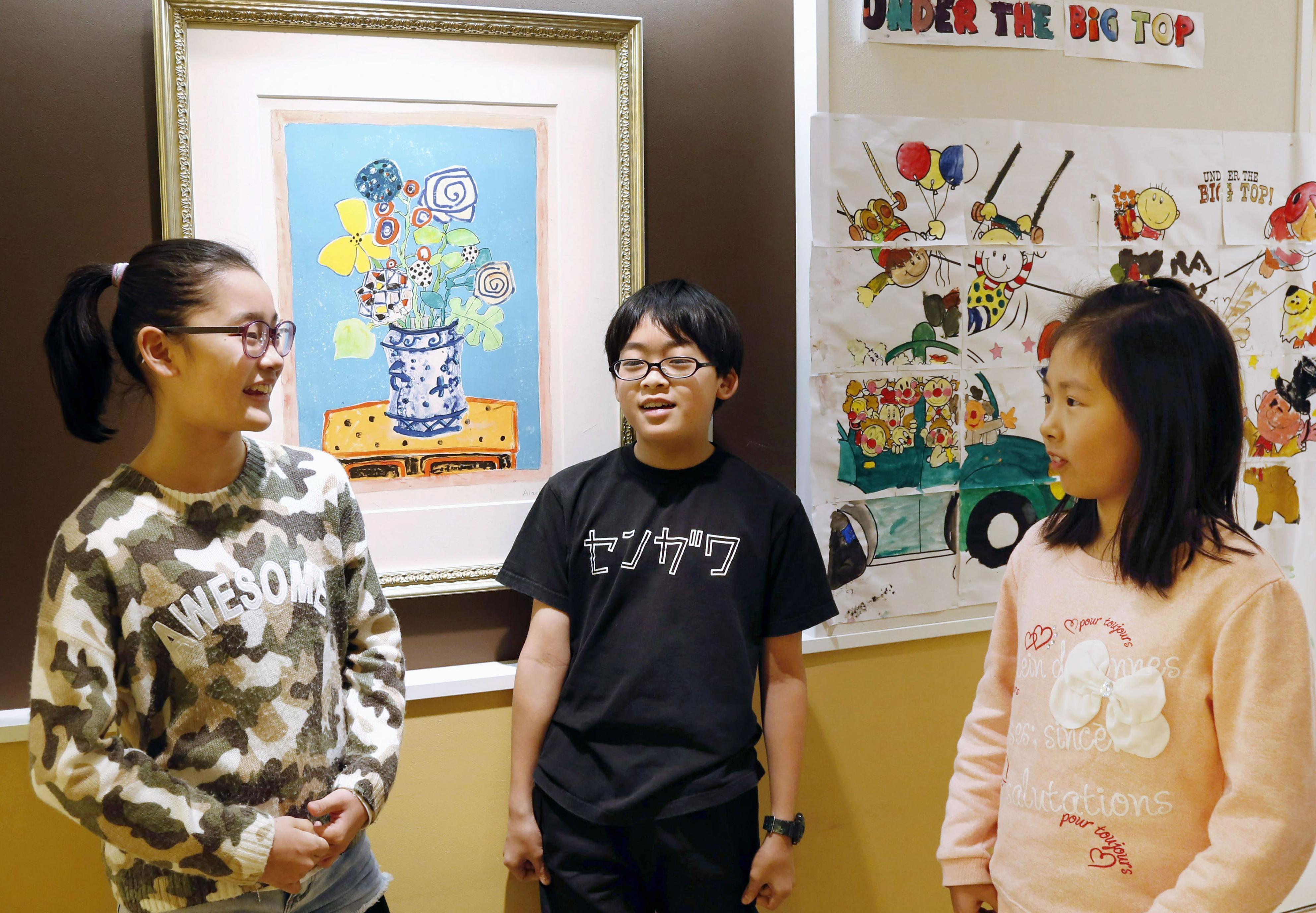 LCA国際小学校の校舎内に飾られた絵画の前で談笑する桜田麗実菜(左)ら=相模原市