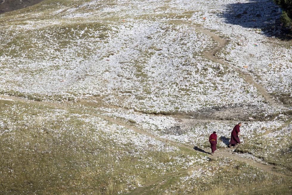 中国・四川省で、僧院近くにある丘を歩く僧侶。雪のように見えるのは、人びとが祈りと願いをこめてまく紙のお札。空を駆け上がり仏神に願いを届けると信じられている「ルンタ(風の馬)」が描かれている(撮影・高橋邦典、共同)