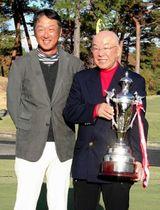 総合優勝を飾り、カップを掲げるアマチュアの岩崎一明(右)とプロの部を制した秋葉真一