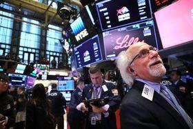 ニューヨーク証券取引所のトレーダーたち=23日(ゲッティ=共同)