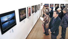 北國写真展の入賞作に目を凝らす来場者=金沢21世紀美術館