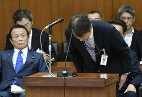 衆院財務金融委員会で謝罪し、頭を下げる金融庁の三井秀範企画市場局長。左は麻生財務相=14日午後