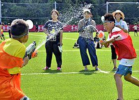 いわきFCフィールドで水鉄砲合戦を楽しむ子どもたち