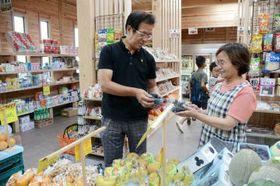 7月28日に再オープンした「中田商店」に立つ中田博之さん、明美さん夫婦=13日、御船町