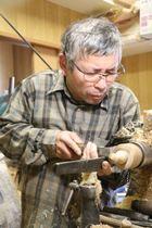 回転する木材にのみを当て、こまを製作する河原さん=長崎市矢の平3丁目