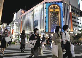 3度目の緊急事態宣言で、休業要請の対象となる大型商業施設が並ぶ銀座を行き交う人たち=23日午後7時26分、東京都中央区で