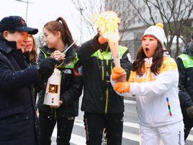 ソウルでの聖火リレーの開始前にトーチに点火してもらう第1走者のパク・ヒジンさん(右端)=13日(共同)
