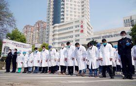 中国・武漢の病院前で、新型コロナウイルスによる死者を哀悼し、黙とうする人たち=4日(新華社=共同)