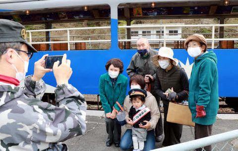 奥出雲おろち号の前で、地元住民や乗客と記念撮影をする初ちゃん