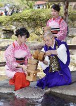 独鈷の湯で僧侶から手おけに湯を受ける湯くみ娘たち=21日午後、静岡県伊豆市の修善寺温泉